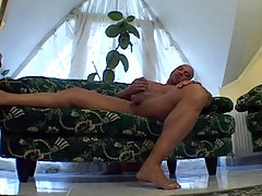 Big tan dude is jerking off on that green couch and cum daddy gay porn